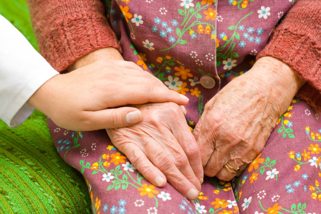 A doctor holding/ shaking an old womans hand - part of a series.