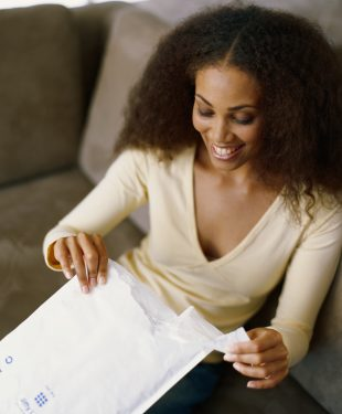 Young woman opening envelop, smiling, elevated view